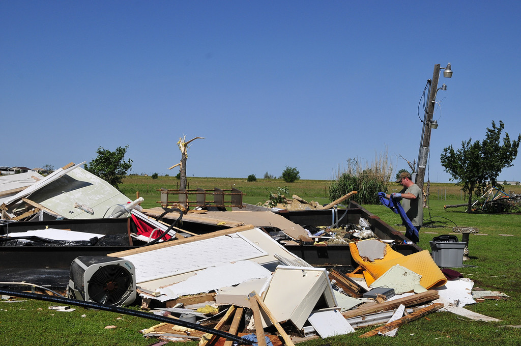 . An El Reno, Okla. resident searches through the wreckage of a friend\'s mobile home hoping to find undamaged belongings in El Reno on Saturday June 1, 2013. (AP Photo/Nick Oxford)