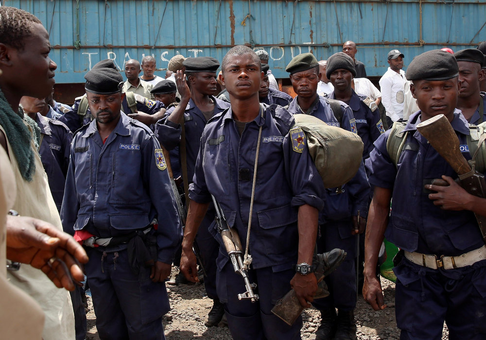 . Police officers stand in a line following the withdrawal of M-23 rebel fighters from Goma December 1, 2012. Rebel fighters, singing and brandishing weapons, pulled out of Democratic Republic of Congo\'s eastern border city of Goma on Saturday, raising hopes regional peace efforts could advance negotiations to end the insurgency.   REUTERS/Goran Tomasevic