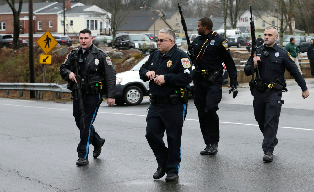 . Police officers cross the road after searching a strip mall near an elementary school, which was in a lockdown, in Ridgefield, Conn., Monday, Dec. 17, 2012, after a suspicious person was seen near a train station close by. On Friday, authorities say a gunman killed his mother at their home and then opened fire inside the Sandy Hook Elementary School in Newtown, killing 26 people, including 20 children, before taking his own life. (AP Photo/Charles Krupa)