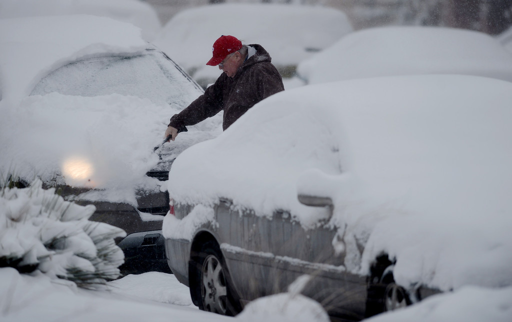 . DENVER, CO. - MARCH 23: Larry Rhine from Pennsylvania is moving snow from his car while visiting his son in Denver. Denver, Colorado. March 23, 2013. (Photo By Hyoung Chang/The Denver Post)