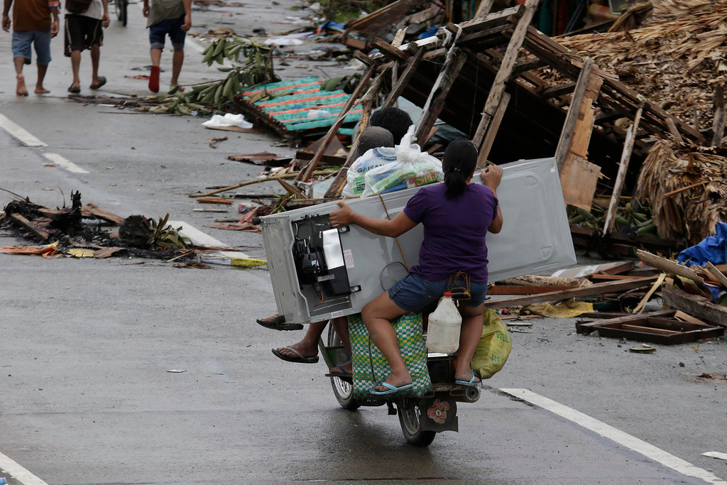 . A resident holds a refrigerator as they drive home Tuesday, Nov. 12, 2013 in Tacloban city in, Leyte province in central Philippines. Four days after Typhoon Haiyan devastated islands in the central Philippines, survivors are desperate for food and clamoring to be evacuated. (AP Photo/Bullit Marquez)