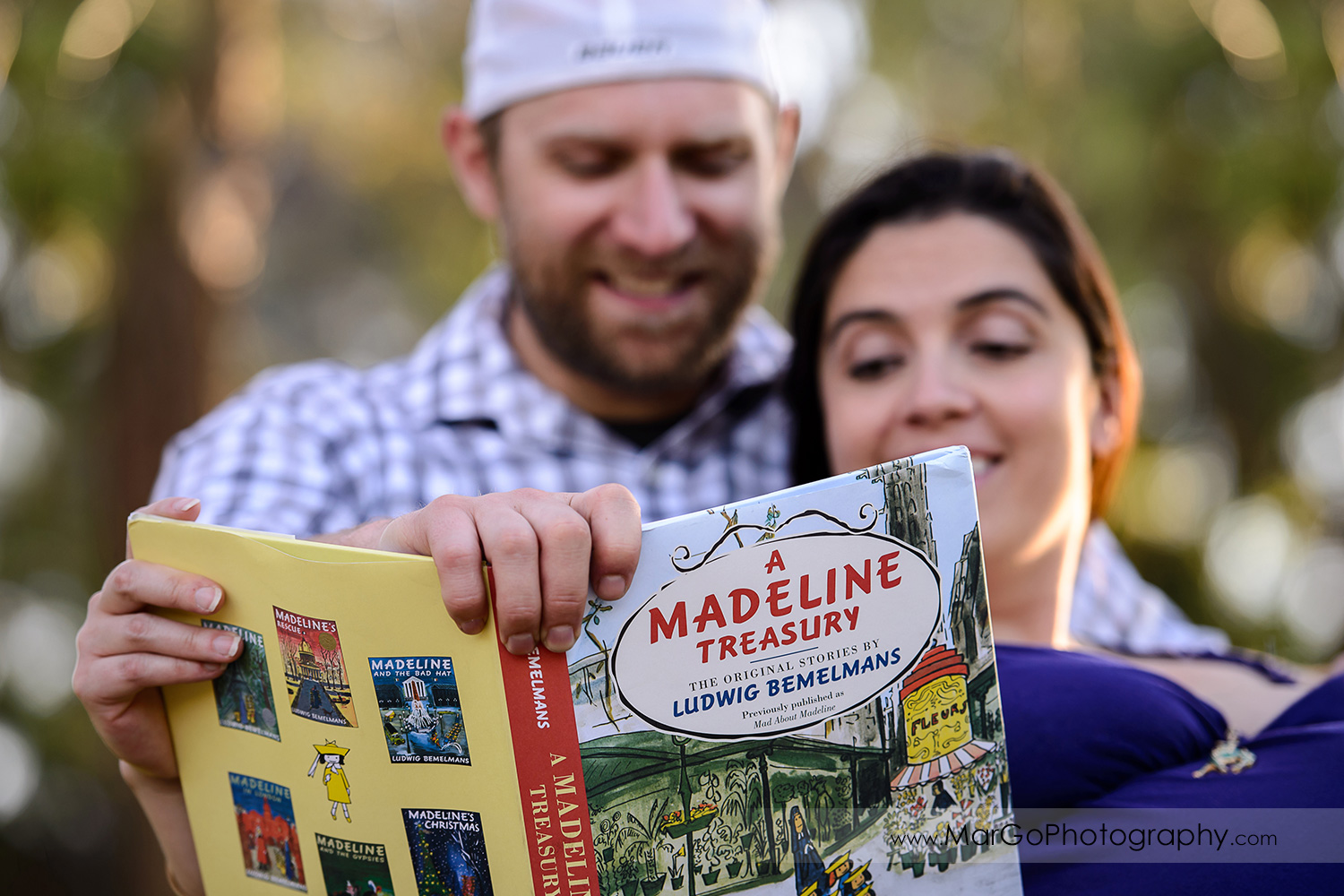 close-up of man in checkered shirt and pregnant woman in long violet dress sitting on the bench and reading children book during maternity session at Lick Mill Park in Santa Clara