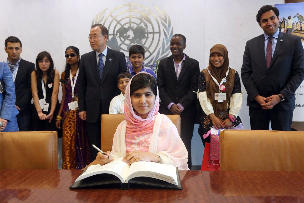 . Malala Yousafzai signs United Nations Secretary-General Ban Ki-moon\'s guest books as Ban Ki-moon, center, and youth delegates look on, Friday, July 12, 2013 at United Nations headquarters. Malala Yousafzai, the Pakistani teenager shot by the Taliban for promoting education for girls, will celebrated her 16th birthday on Friday addressing the United Nations. (AP Photo/Mary Altaffer)
