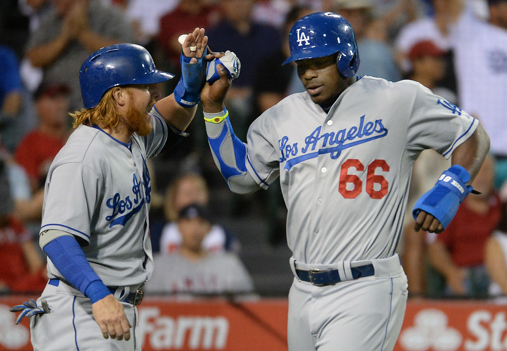 . Los Angeles Dodgers\' Justin Turner, left, high fives teammate Yasiel Puig (66) after scoring on a two RBI single by Hanley Ramirez (not pictured) in the third inning of a baseball game against the Los Angeles Angels at Anaheim Stadium in Anaheim, Calif., on Thursday, Aug. 7, 2014.  (Photo by Keith Birmingham/ Pasadena Star-News)