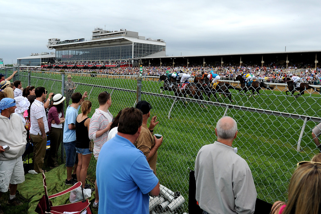 . BALTIMORE, MD - MAY 18:  Fans watch as horses race down the turf frontstetch in the Fifth race prior to the 138th running of the Preakness Stakes at Pimlico Race Course on May 18, 2013 in Baltimore, Maryland.  (Photo by Patrick Smith/Getty Images)