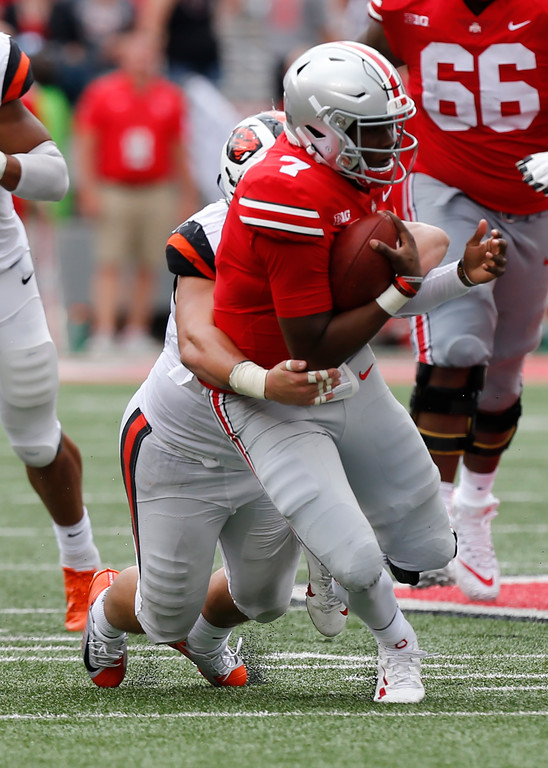 . Ohio State quarterback Dwayne Haskins is tackled by Oregon State defensive lineman Isaac Hodgins during the second half of an NCAA college football game Saturday, Sept. 1, 2018, in Columbus, Ohio. Ohio State beat Oregon State 77-31. (AP Photo/Jay LaPrete)