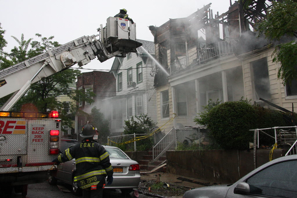 . Firefighters continue working the scene of a fire that tore through three townhouses on New York City\'s Staten Island early Thursday, June 5, 2014. (AP Photo/Staten Island Advance, Irving Silverstein)