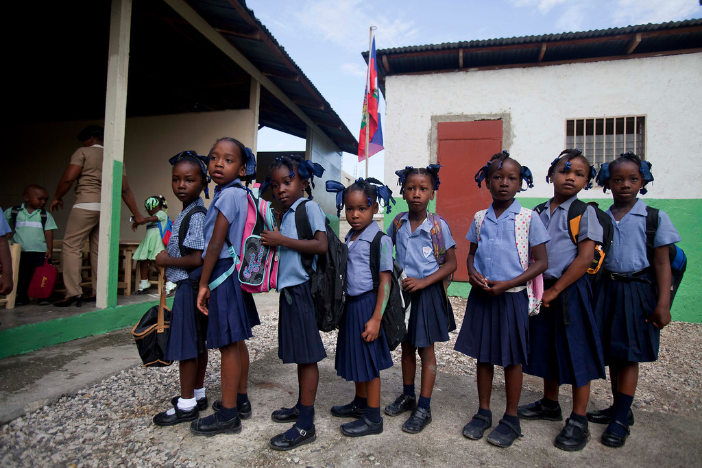 . In this Tuesday, Oct. 1, 2013 photo, students stand in line on the first day of classes at the National School of Republique des Etats-Unis d\'Amerique in Port-au-Prince, Haiti. Schools in Haiti opened their doors one month late, to allow parents more time to pay for their children\'s academic records from the previous year; a prerequisite to enroll in the current school year. (AP Photo/Dieu Nalio Chery)