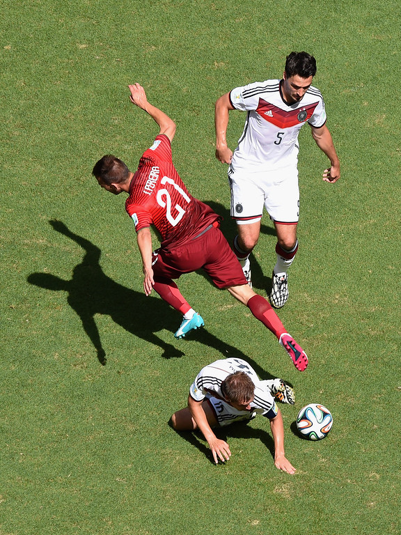 . Philipp Lahm of Germany tackles Joao Pereira of Portugal as Mats Hummels of Germany looks on during the 2014 FIFA World Cup Brazil Group G match between Germany and Portugal at Arena Fonte Nova on June 16, 2014 in Salvador, Brazil.  (Photo by Francois Xavier Marit - Pool/Getty Images)