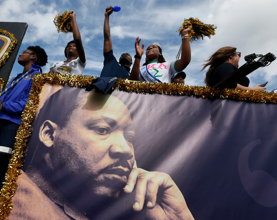 . People aboard a float from Florida International University wave to crowds during a parade honoring Dr. Martin Luther King Jr., Monday, Jan. 16, 2017, in the Liberty City neighborhood of Miami. (AP Photo/Wilfredo Lee)