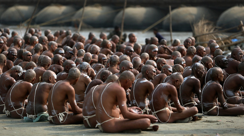 """. Hindu holy men of the Juna Akhara sect sit after rituals that are believed to rid them of all ties in this life and dedicate themselves to serving God as a \""""Naga\"""" or naked holy men, at Sangam, the confluence of the Ganges and Yamuna River during the Maha Kumbh festival in Allahabad, India, Wednesday, Feb. 6, 2013. The significance of nakedness is that they will not have any worldly ties to material belongings, even something as simple as clothes. This ritual that transforms selected holy men to Naga can only be done at the Kumbh festival.(AP Photo /Manish Swarup)"""