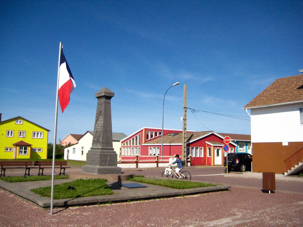 Flagpole flying the french flag in a square on the island of St. Pierre.