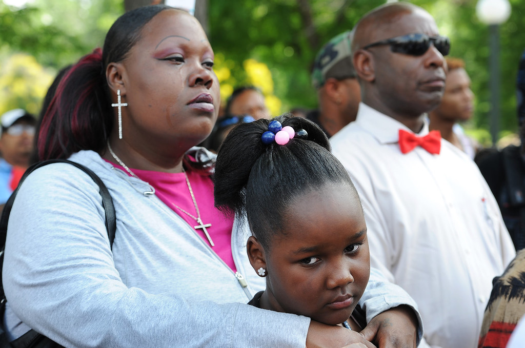""". Torri Morris, 11, stays close in the arms of her mother Tamesah Morris, during the rally in City Park in Denver, CO on July 14, 2013.  Members of the African American community turned out for a rally  to show their disappointment in the acquittal of George Zimmerman in the murder trail of Trayvon Martin on July 14, 2013. Zimmerman is the Florida man who shot and killed Trayvon Martin. \""""We will not erase the conversation of race,\"""" said Jeff Fard, founder of Brother Jeff\'s Cultural Center in the Five Points neighborhood. \""""Don\'t be afraid to say if Trayvon Martin was a white man he would be alive today.\""""  Photo by Helen H. Richardson/The Denver Post)"""