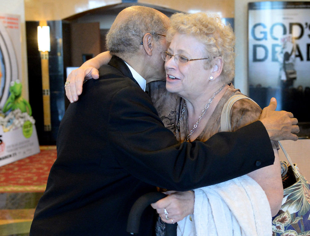 . Al Harris, floor manager of the Krikorian Premier Theatre, hugs Ching Trenchard of San Bernardino, Thursday, in Redlands,Ca., Feb. 13, 2014. Harris has become a local icon collecting tickets and giving high fives to moviegoers since being hired by Krikorian in 1992.  (John Valenzuela/Photographer)