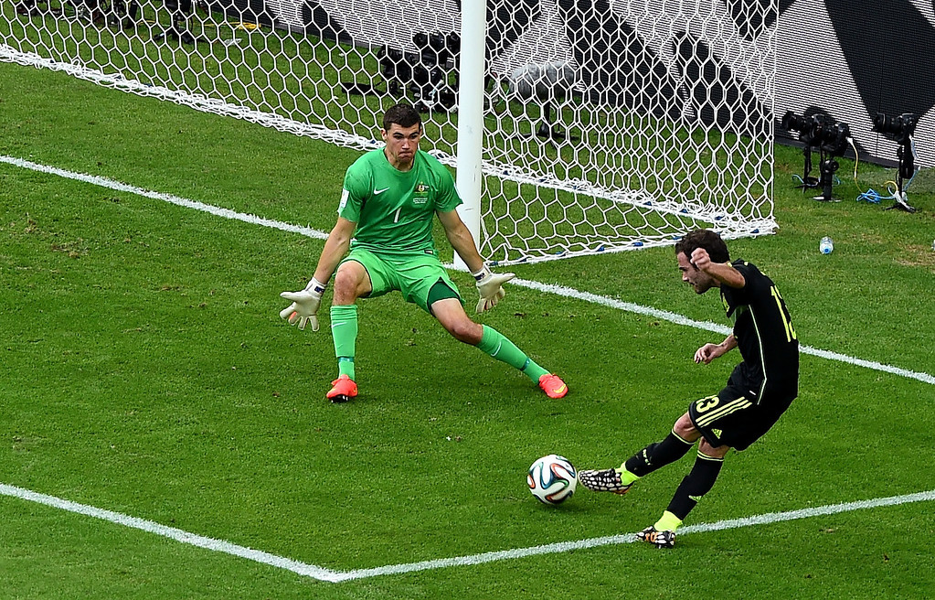 . Juan Mata of Spain scores his team\'s third goal past Mathew Ryan of Australia during the 2014 FIFA World Cup Brazil Group B match between Australia and Spain at Arena da Baixada on June 23, 2014 in Curitiba, Brazil.  (Photo by David Ramos/Getty Images)