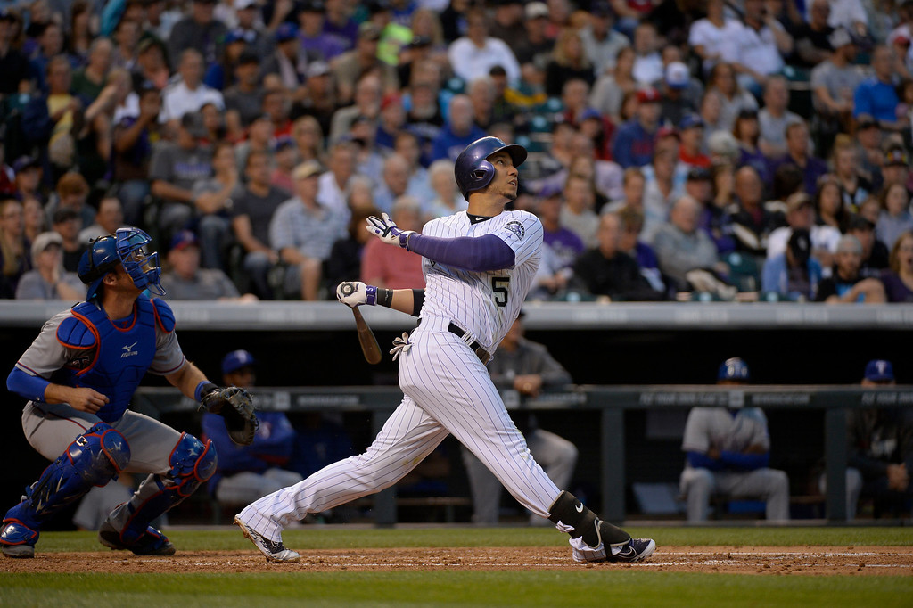 . DENVER, CO - MAY 06: Colorado Rockies left fielder Carlos Gonzalez (5) singles on a fly ball to left field off of Texas Rangers starting pitcher Robbie Ross (46) in the third inning May 6, 2014 at Coors Field. (Photo by John Leyba/The Denver Post)