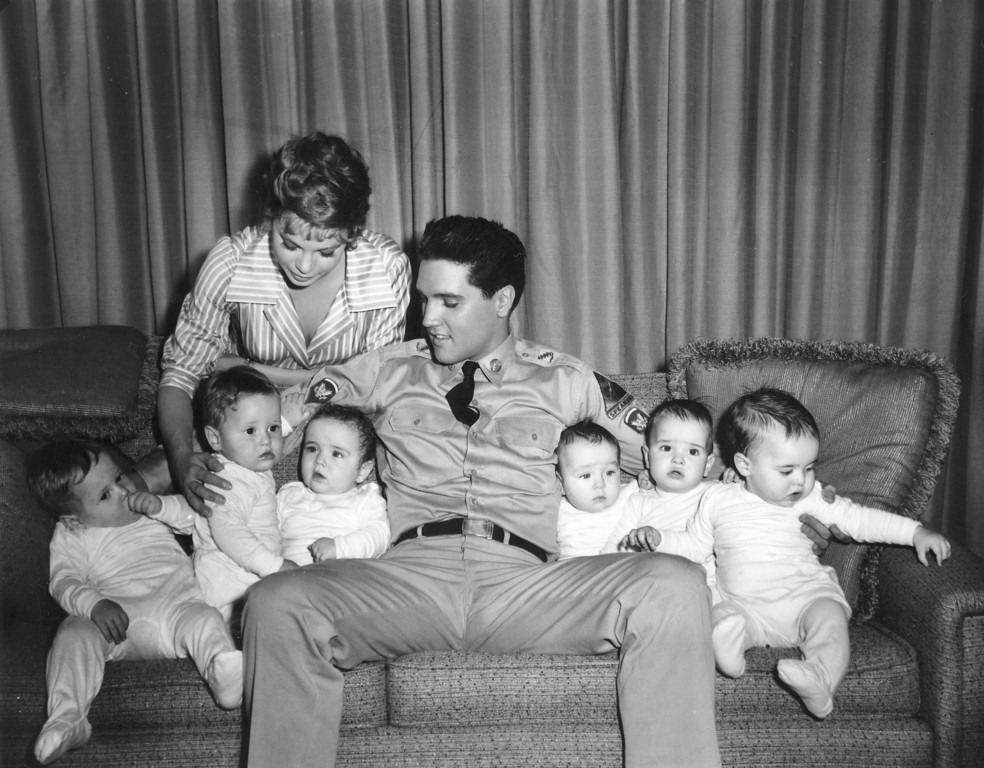 ". Singer-actor Elvis Presley is shown with six babies who appear in the movie ""G.I. Blues\"" and co-star Juliet Prowse, left, on a set in Hollywood, Ca., on June 27, 1960.  The babies are three sets of twins who double for one another in the movie.  (AP Photo)"
