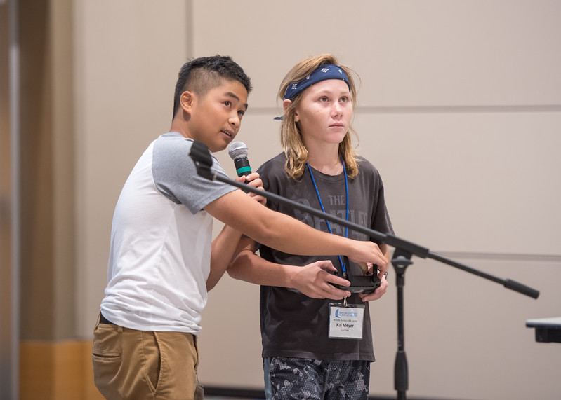 UAS camp attendee Kai Meyer flies a quadcoptor drone with the help of student Vincent Nguyen.