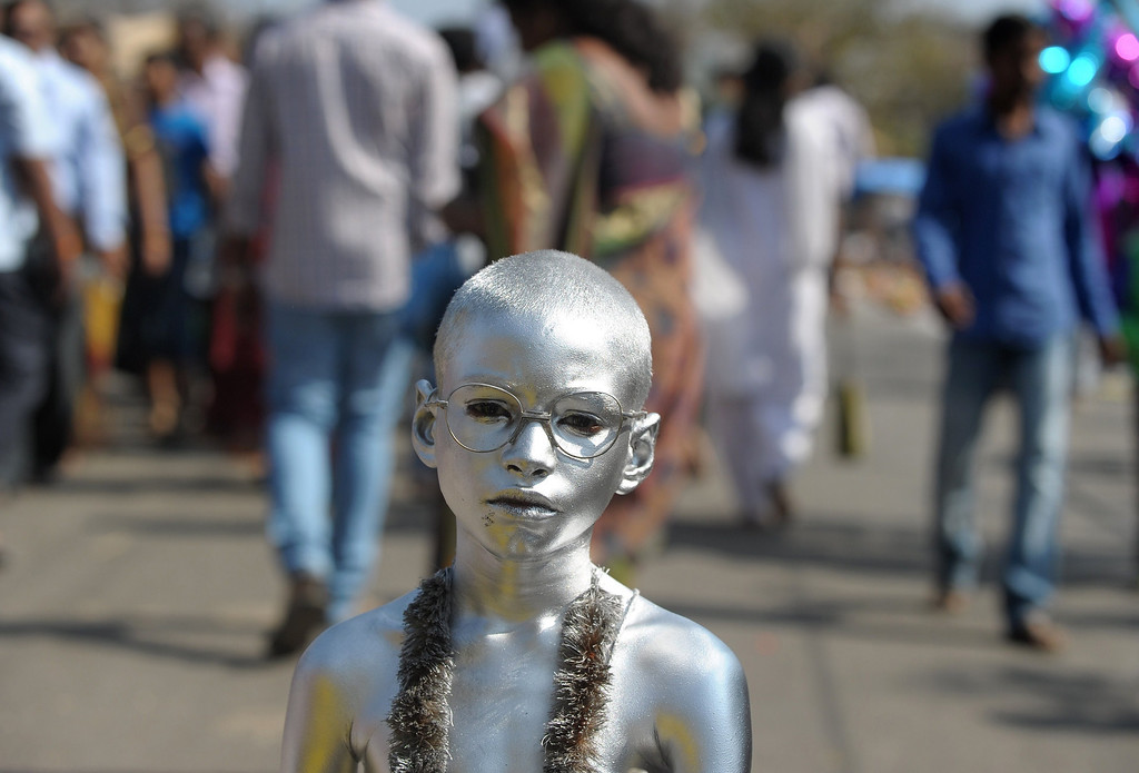 . An Indian boy dressed as Mahatma Gandhi begs for alms from Hindu devotees during the Maha Shivaratri festival outside the Keesaragutta Temple on the outskirts of Hyderabad on February 27, 2014. T AFP PHOTO/Noah  SEELAM/AFP/Getty Images
