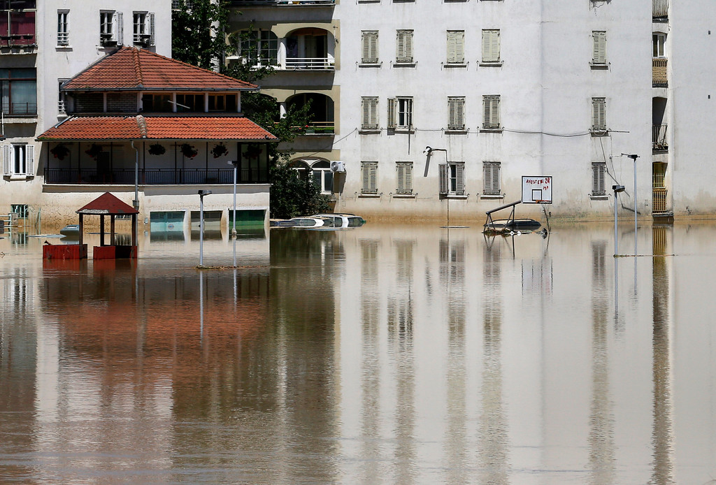. Buildings are reflected in a flooded street in Obrenovac, some 30 kilometers (18 miles) southwest of Belgrade, Serbia, Monday, May 19, 2014. Belgrade braced for a river surge Monday that threatened to inundate Serbia\'s main power plant and cause major power cuts in the crisis-stricken country as the Balkans struggle with the consequences of the worst flooding in southeastern Europe in more than a century. At least 35 people have died in Serbia and Bosnia in the five days of flooding caused by unprecedented torrential rain, laying waste to entire towns and villages and sending tens of thousands of people out of their homes, authorities said. (AP Photo/Darko Vojinovic)