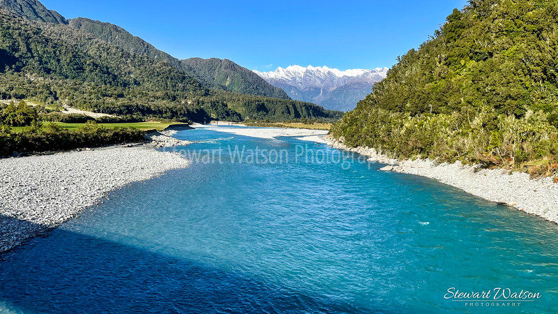 The blue waters of the Whataroa river winging its way to the Alps