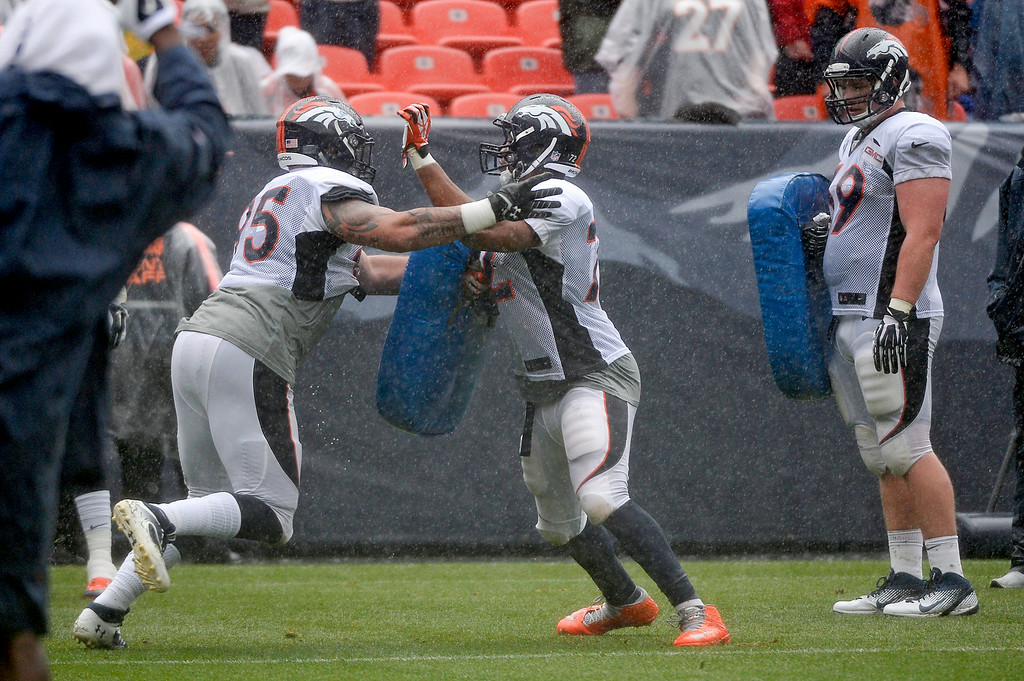 . Denver Broncos defensive end Derek Wolfe (95) runs through drills with Denver Broncos defensive end Hall Davis (72) during a rain day on day six of the Denver Broncos 2014 training camp July 30, 2014 at Sports Authority Field at Mile High Stadium.  (Photo by John Leyba/The Denver Post)