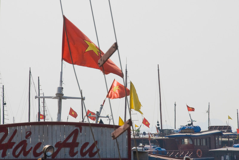 Flags waving on top of boats - Ha Long Bay, Vietnam