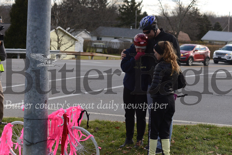 "Christina Teimouri, left, is consoled as she is overcome with emotion while visiting the site of a ""ghost bike"" memorial for her son, Alek."