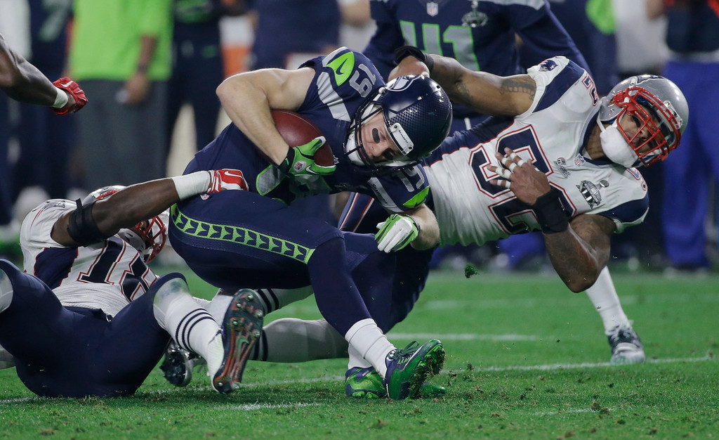 . Seattle Seahawks\' Bryan Walters (19) is tackled by New England Patriots\' Matthew Slater (18) and Jonathan Casillas (52) on a punt return during the second half of NFL Super Bowl XLIX football game Sunday, Feb. 1, 2015, in Glendale, Ariz. (AP Photo/Mark Humphrey)