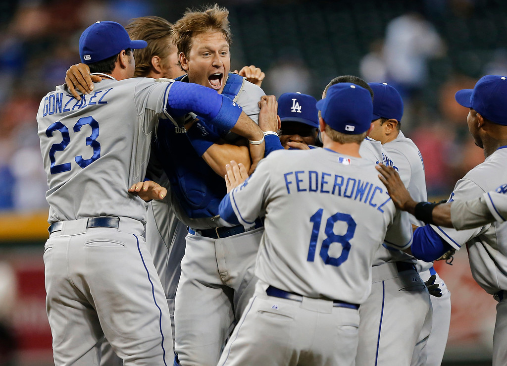 . The Los Angeles Dodgers celebrate a 7-6 win over the Arizona Diamondbacks in a baseball game, Thursday, Sept. 19, 2013, in Phoenix. The Dodgers clinched the N.L. West title. (AP Photo/Matt York)
