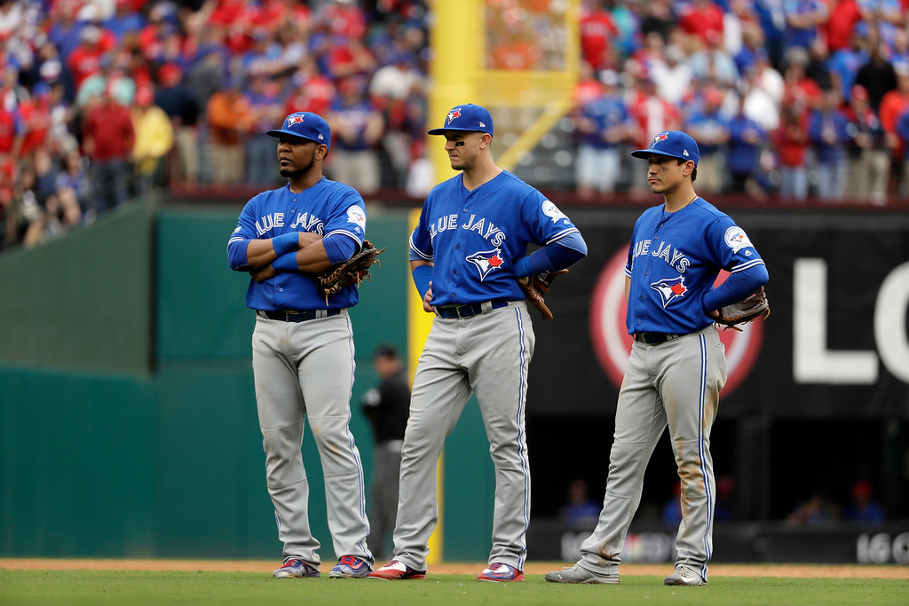 . Toronto Blue Jays\' Edwin Encarnacion, Troy Tulowitzki and Darwin Barney, right, stand on the field in the eighth inning of Game 2 of baseball\'s American League Division Series against the Texas Rangers on Friday, Oct. 7, 2016, in Arlington, Texas. (AP Photo/David J. Phillip)