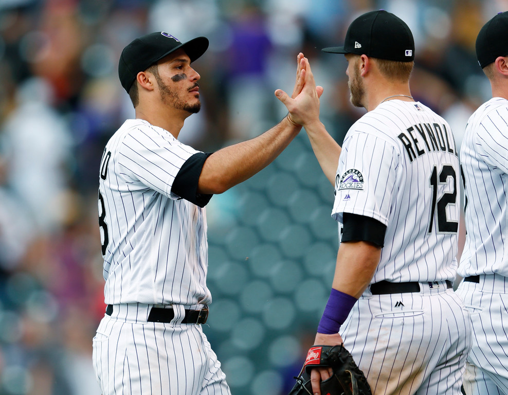 . Colorado Rockies third baseman Nolan Arenado, left, and first baseman Mark Reynolds celebrate after the Rockies defeated the Cleveland Indians 8-1 in a baseball game Wednesday, June 7, 2017, in Denver. (AP Photo/David Zalubowski)