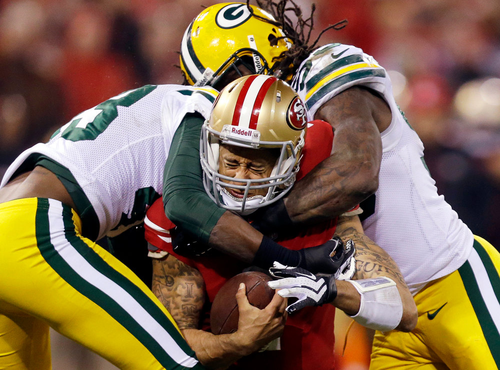 Description of . San Francisco 49ers quarterback Colin Kaepernick (7) is tackled by Green Bay Packers free safety M.D. Jennings (43) and outside linebacker Erik Walden (93) during the second quarter of an NFC divisional playoff NFL football game in San Francisco, Saturday, Jan. 12, 2013. (AP Photo/Marcio Jose Sanchez)