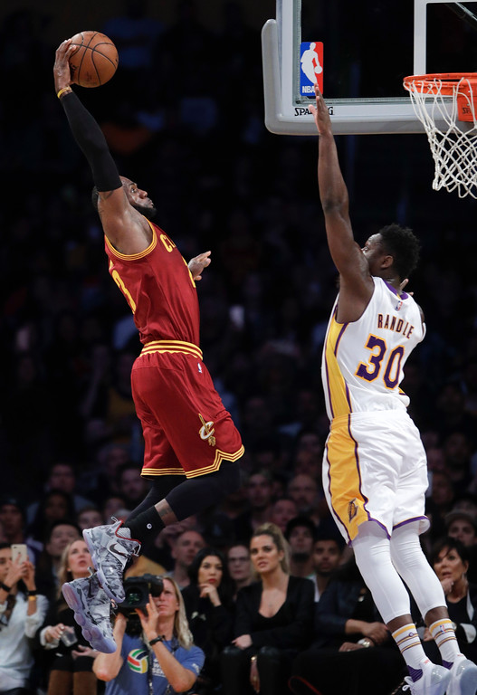 . Cleveland Cavaliers\' LeBron James, left, goes up for a dunk under defense by Los Angeles Lakers\' Julius Randle during the first half of an NBA basketball game Sunday, March 19, 2017, in Los Angeles. (AP Photo/Jae C. Hong)