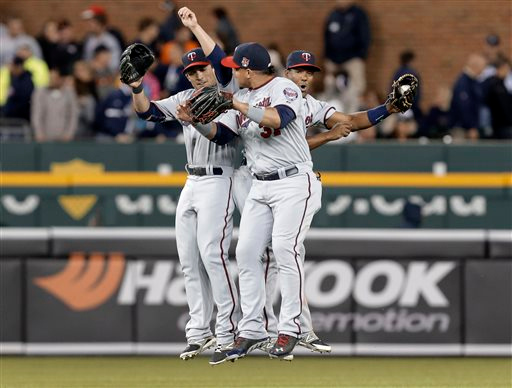 . From left to right, Minnesota Twins outfielders Sam Fuld, Oswaldo Arcia and Danny Santana celebrate after their 2-0 victory over the Detroit Tigers in a baseball game in Detroit, Friday, June 13, 2014. (AP Photo/Paul Sancya)