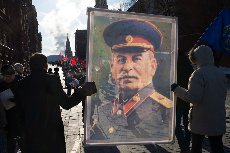. Communist supporters carry a portrait of Soviet dictator Josef Stalin as they line up to place flowers on Stalin\'s grave in Red Square, outside the Kremlin wall to mark the 60th anniversary of his death, in Moscow, Russia, Tuesday, March 5, 2013. Stalin led the Soviet Union from 1924 until his death in 1953. Communists credit him with leading the country to victory in World War II while others condemn the brutal purges that killed millions. (AP Photo/Alexander Zemlianichenko)