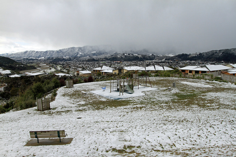 Childrens playground in Riverstone, with snow shower moving across Upper Hutt in the background - Monday 15th August 2011.