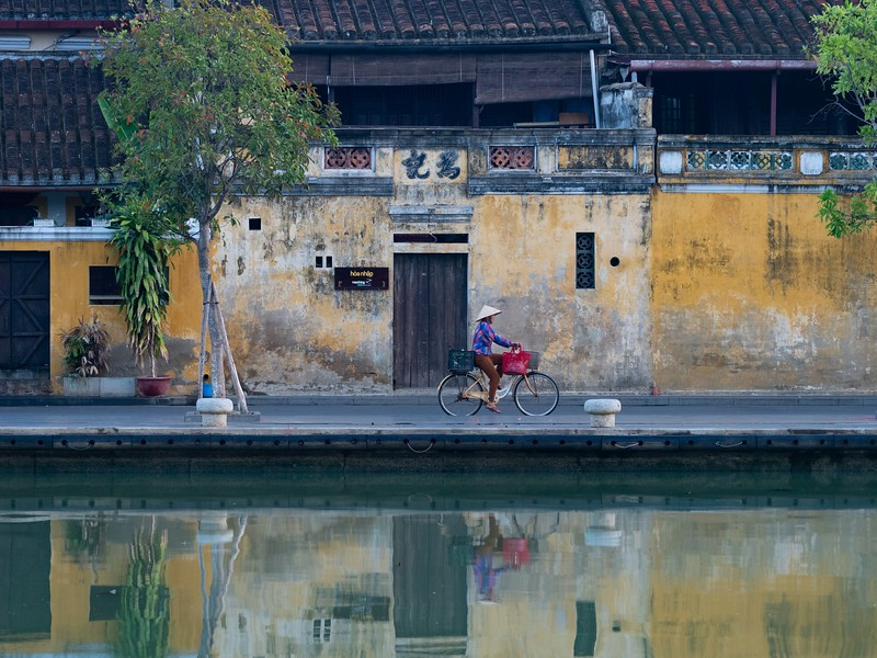 Woman Riding a Bike Along a River in Hoi An, Vietnam