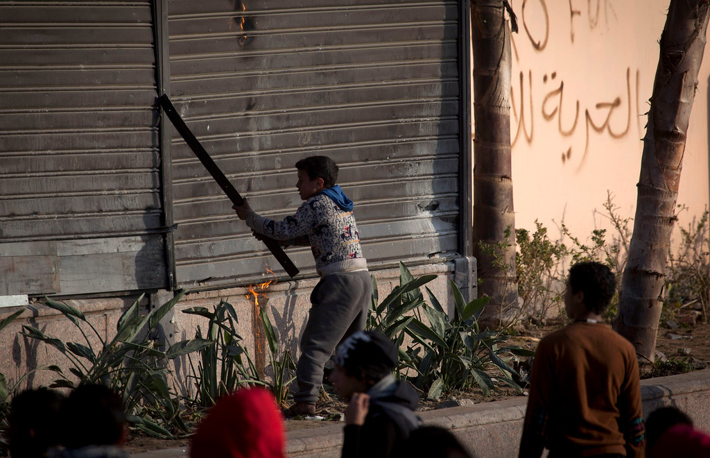 . A young Egyptian protester smashes the front of a hotel during clashes with riot police in downtown Cairo, Egypt, Saturday, March 9, 2013. (AP Photo/Nasser Nasser)