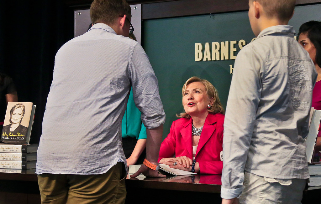 ". Joseph Rodgers, 18, left, a high school senior from Pittsburgh, Pa., chats with HiIlary Clinton, center, before receiving a signed copy of her new book  ""Hard Choices,\"" on Tuesday June 10, 2014, at Barnes and Noble bookstore in New York.  (AP Photo/Bebeto Matthews)"