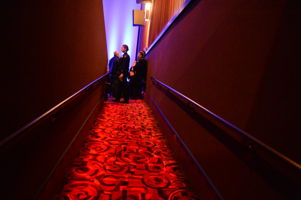 Description of . AURORA, CO. - JANUARY 17:  An Aurora Police officer walks into  the reopening and remembrance in Theater I XD  of the Century Aurora Theater. James Holmes is accused of killing 12 people and wounding 70 others on July 20, 2012 in theater 9. (Photo By RJ Sangosti / The Denver Post)