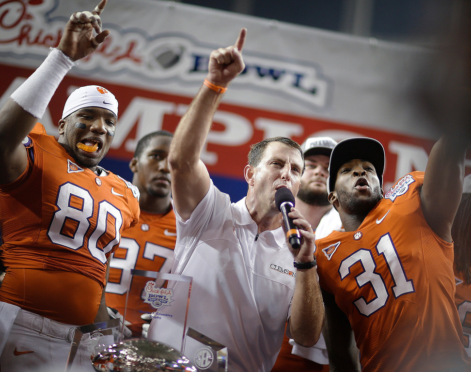. Clemson coach Dabo Swinney speaks to fans with safety Rashard Hall (31) and tight end Brandon Ford (80) after the Chick-fil-A Bowl NCAA college football game against LSU, Monday, Dec. 31, 2012, in Atlanta. Clemson won 25-24. (AP Photo/David Goldman)