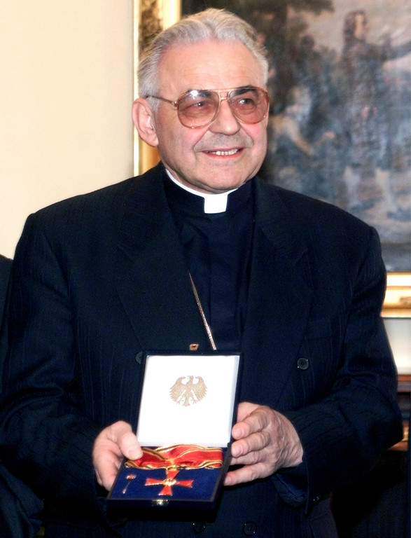 . FILE - This Feb. 25, 1999 file photo shiws Prague Cardinal Miloslav Vlk holding the Order of the Federal Republic of Germany, in Berlin, Germany, Thursday, Feb. 25, 1999. Vlk, who, when a priest during communist rule in Czechoslovakia, was forced to clandestinely minister to Catholics while officially working as a window-washer in the city, has died Saturday, March 18, 2017 at the age of 84. (AP Photo/Christof Stache)