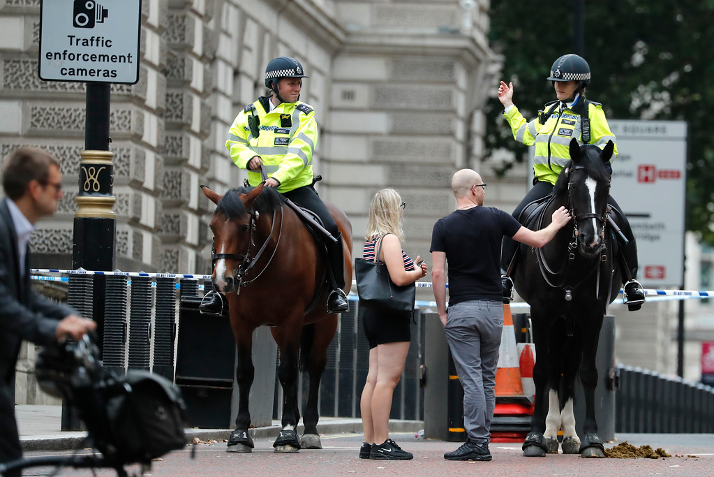 . Mounted police officers block a road leading to the scene where a car that crashed into security barriers outside the Houses of Parliament to the right of a bus in London, Tuesday, Aug. 14, 2018. London police say that a car has crashed into barriers outside the Houses of Parliament and that there are a number of injured. (AP Photo/Frank Augstein)