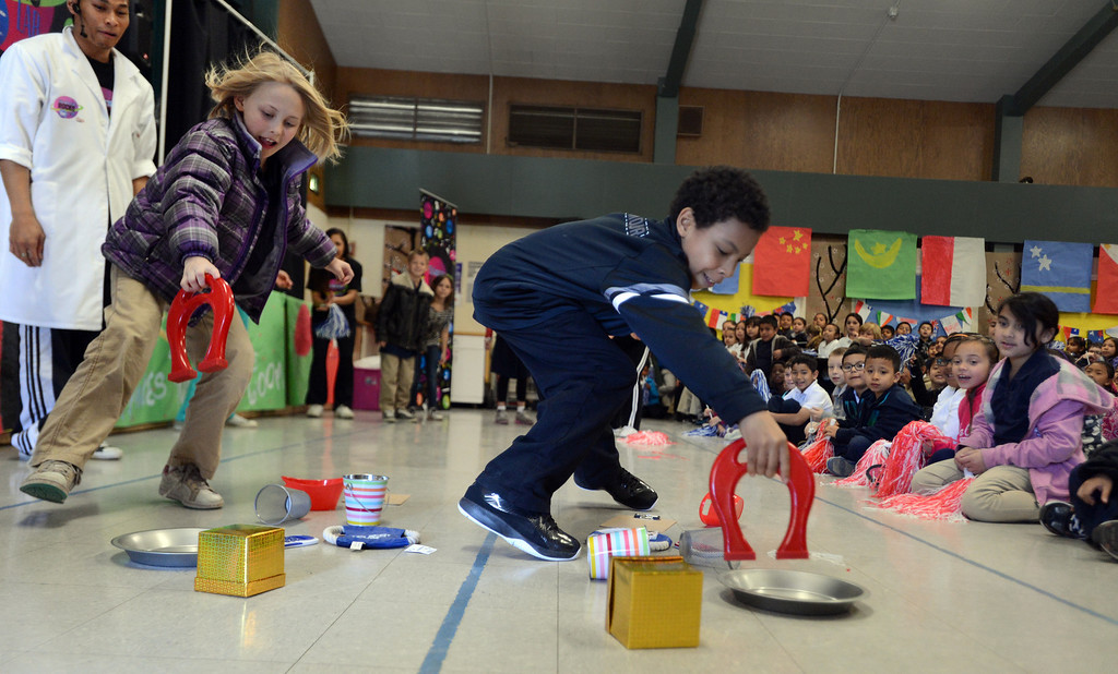 ". Third-graders Maggie Sharpe, left, and Rick Camacho race to pick up items with a magnet during a ""Science Rocks\"" program held at El Monte Elementary School in Concord, Calif., on Tuesday, Feb. 26, 2013.  (Susan Tripp Pollard/Staff)"