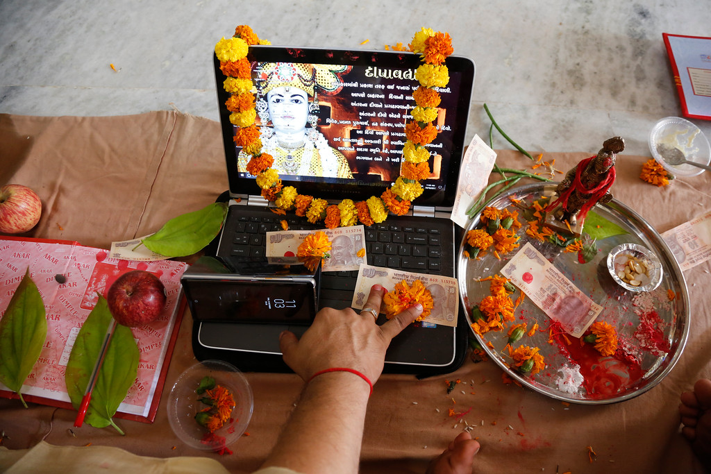 . An Indian businessman performs rituals during Chopada Pujan, or a mass prayer ceremony dedicated to the worship of the account book, on the occasion of Diwali, the Hindu festival of lights, in Ahmadabad, India, Thursday, Oct. 19, 2017. During Chopada Pujan, ledgers and new account books are opened by the mercantile community following a special prayer and worship before the idols of Lord Ganesha and Hindu Goddess of wealth Lakshmi to earn their blessings. (AP Photo/Ajit Solanki)