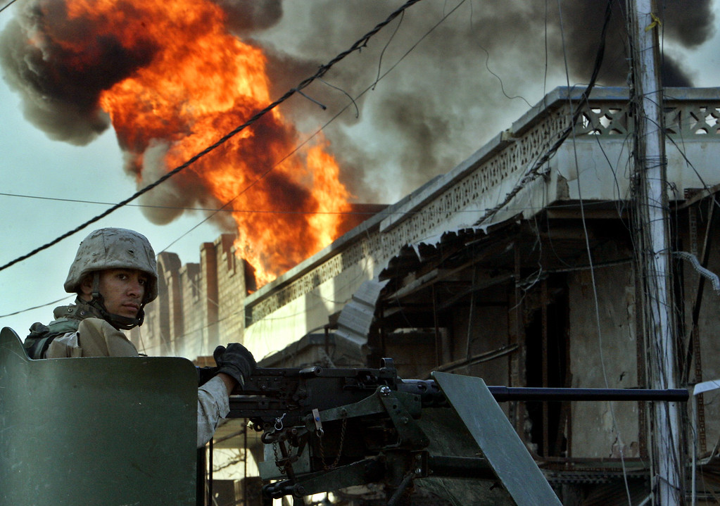 """. A U.S. Marine of the first Division passes by a burning house in the western part of Fallujah, Iraq, Sunday, Nov. 14, 2004. U.S. military officials said Saturday that U.S. Forces had now \""""occupied\"""" the entire city of Fallujah. (AP Photo/Anja Niedringhaus)"""