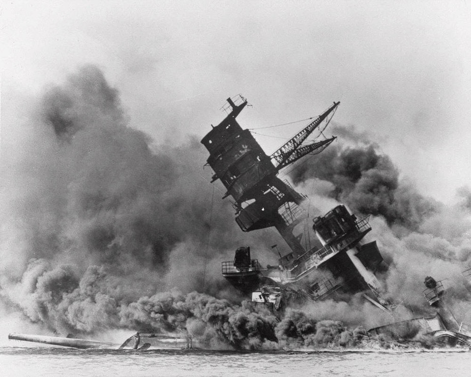 ". The battleship USS Arizona belches smoke as it topples over into the sea during a Japanese surprise attack on Pearl Harbor, Hawaii,  Dec. 7, 1941. The ship sank with more than 80  percent of its 1,500-man crew, including Rear Admiral Isaac C. Kidd . The attack, which left 2,343 Americans dead and 916 missing, broke the backbone of the U.S. Pacific Fleet and forced  America out of a policy of isolationism. President Franklin D. Roosevelt announced that it was ""a date which will live in infamy\"" and Congress declared war on Japan the morning after. This was the  first attack on American territory since 1812. (AP Photo)"