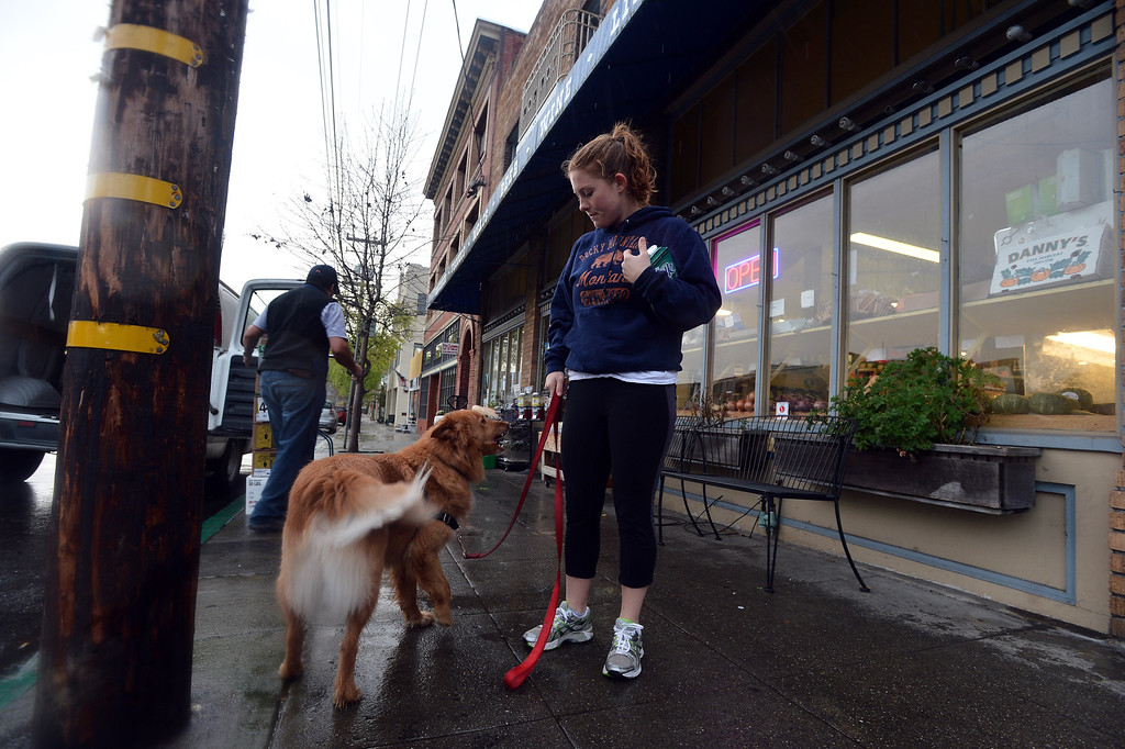 . After picking up some milk at the Santa Fe Market, Ariana Jacobs and her dog Tom get on with their day in the Point Richmond area of Richmond, Calif. on Thursday, Feb. 7, 2013. (Kristopher Skinner/Staff)