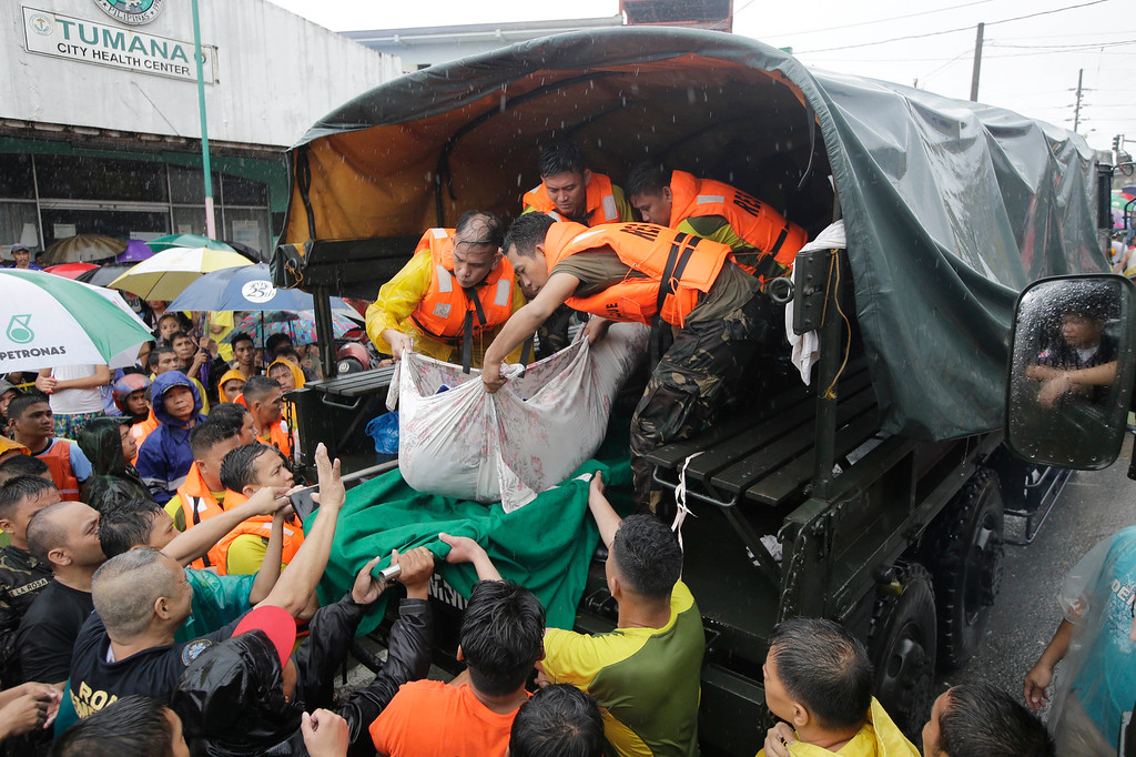 . Rescuers unload the body of a man who died of natural causes at the height of heavy flooding brought about by tropical storm Fung-Wong flooded Marikina city, east of Manila, Philippines and most parts of the metropolis Friday, Sept. 19, 2014. (AP Photo/Bullit Marquez)